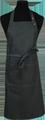 Detail foto van Halterschort voorzien van een dubbel opgestikte zak met rivetten en een verstelbare nekband d.m.v. drukkers. Extra lange strikbanden waardoor het schort voor gestrikt kan worden. - Black Camel